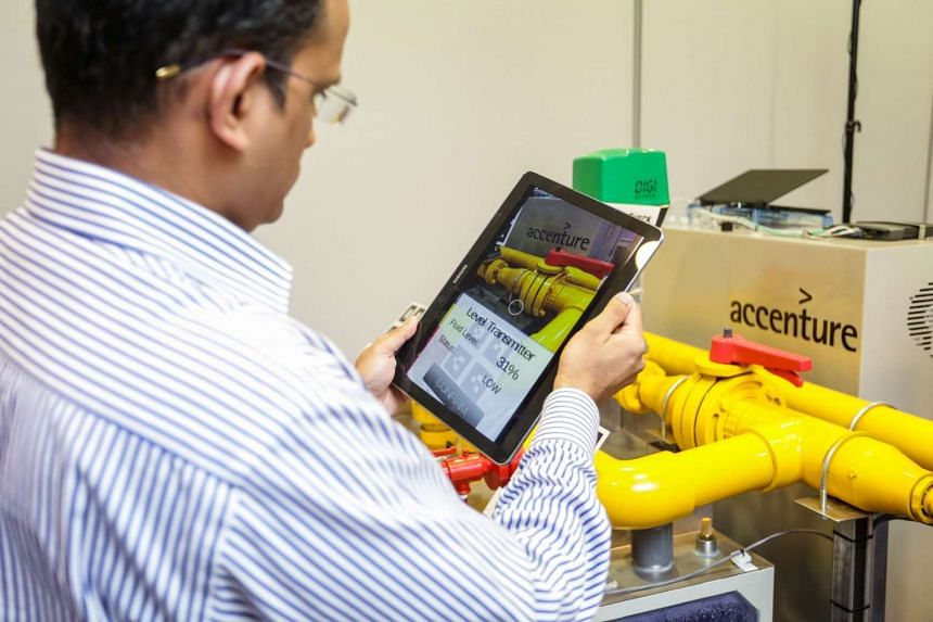 Accenture's Mr Senthil Ramani demonstrates how the smart worker of the future will operate a plant powered by advanced analytics and artificial intelligence. For example, machines can be monitored using smart devices and sensors, as shown above.