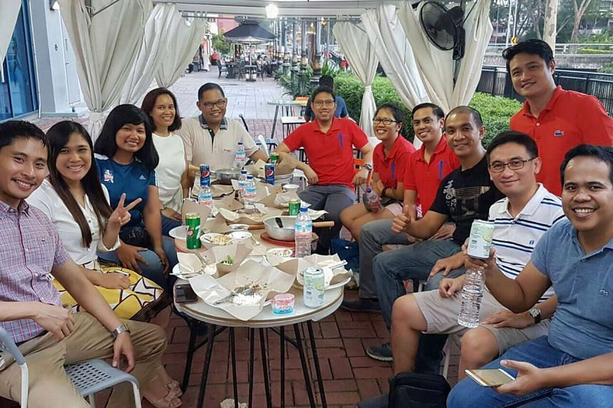 Mr Anthony Garcia (left) gets to chat in Tagalog when he meets his friends from the University of the Philippines Alumni Association in Singapore.