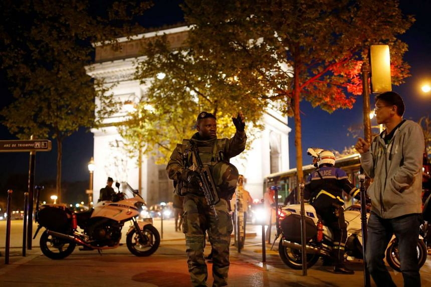 An armed soldier secures a side road near the Champs Elysees Avenue after a policeman was killed and two others were wounded in a shooting incident in Paris, France, on April 20, 2017.