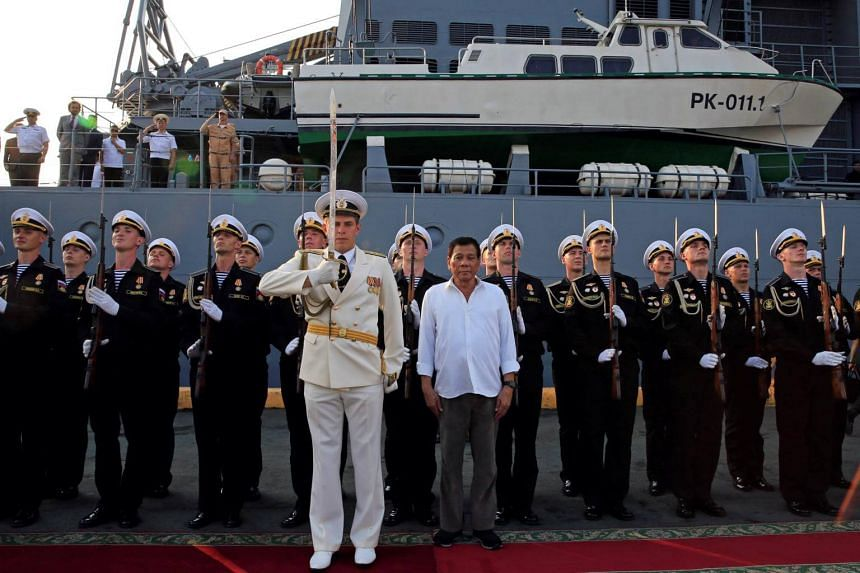 Philippine President Rodrigo Duterte stands to attention after touring Russian Navy guided missile cruiser Varyag, docked during a goodwill visit, at Pier 15, South Harbor, Metro Manila, Philippines on April 21, 2017.