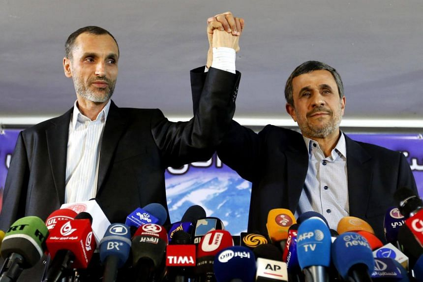 Former Iranian president Mahmoud Ahmadinejad (right) and his former vice president, Hamid Baghaie, lock hands during a press conference in the capital Teheran on April 5, 2017.