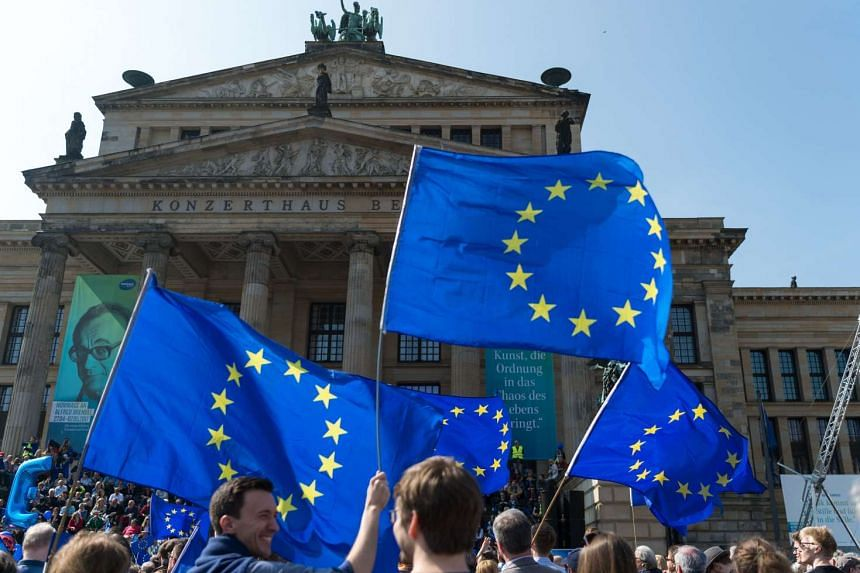 Participants of a Pulse Of Europe rally holding up European flags as they demonstrate on April 9, 2017, in front of the Konzerthaus (concert hall) at Gendarmenmarkt square in Berlin, Germany.