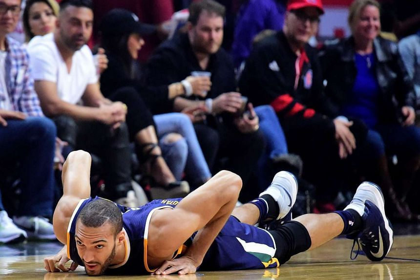 Rudy Gobert #27 of the Utah Jazz lays on the floor after an injury during the first half against the LA Clippers at Staples Center on April 15, 2017 in Los Angeles, California.