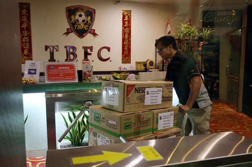 Investigators removing documents from Tiong Bahru Football Club and loading them onto a police van.