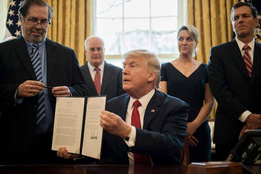 Trump holds up a directive ordering an investigation into the impact of foreign steel on the American economy.