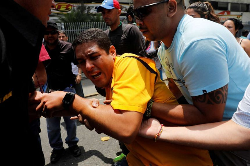 Deputy of the opposition party Justice First (Primero Justicia) Jose Olivares (centre) reacts after he was affected by tear gas.