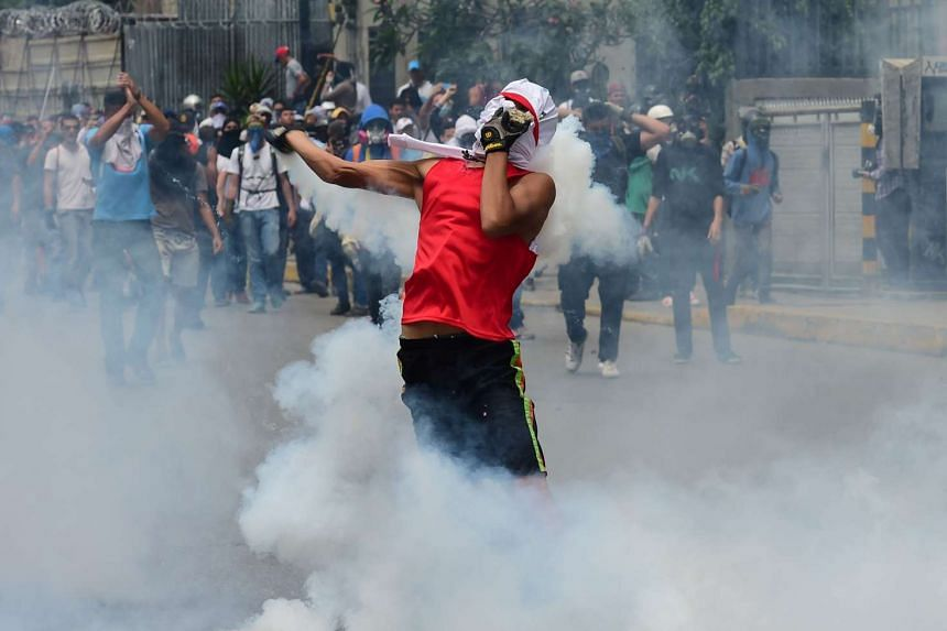 Demonstrators clash with the riot police during a protest against Venezuelan President Nicolas Maduro, in Caracas on April 20, 2017.