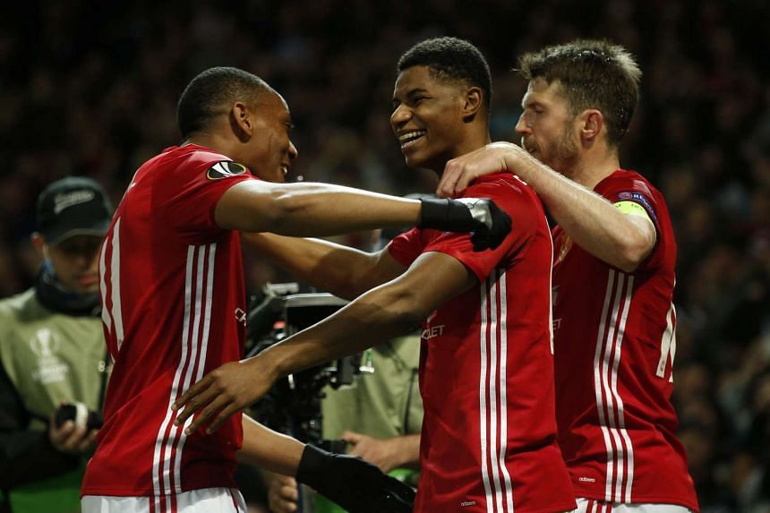 Manchester United's Marcus Rashford celebrates scoring their second goal with Anthony Martial and Michael Carrick.