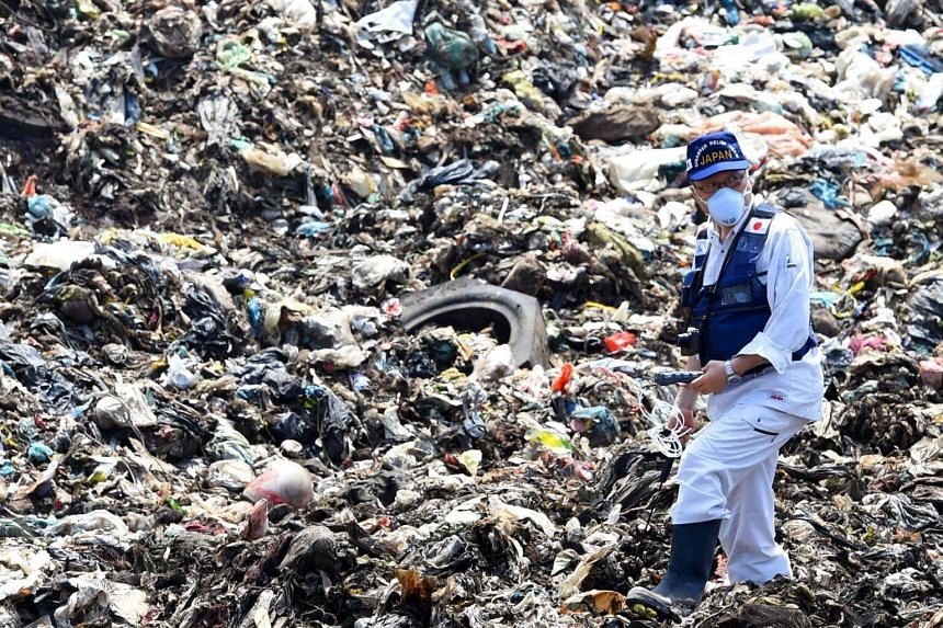 A Japanese official with a disaster relief team surveys the site of a garbage dump collapse that killed 32 people on the northeastern edge of Sri Lanka's capital Colombo on April 21, 2017.