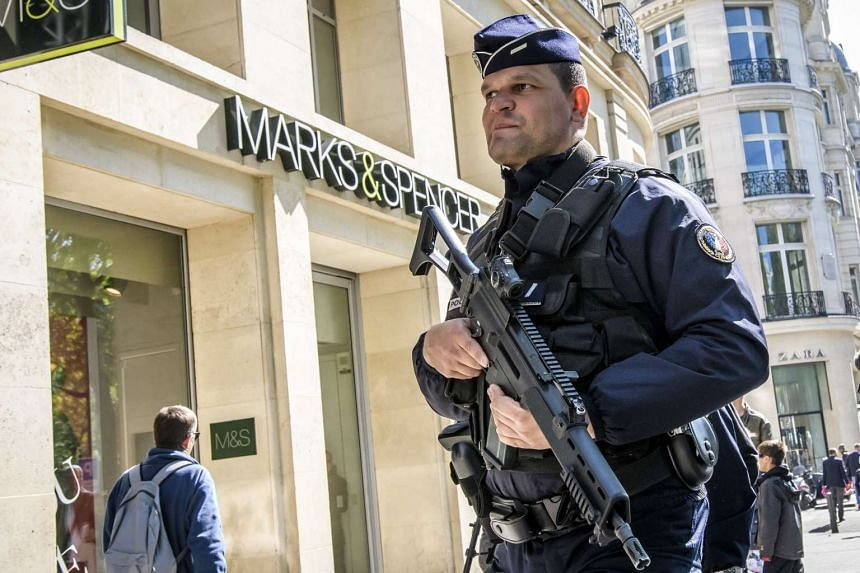 A French policeman patrols at the Champs Elysees avenue in Paris, April 2017.