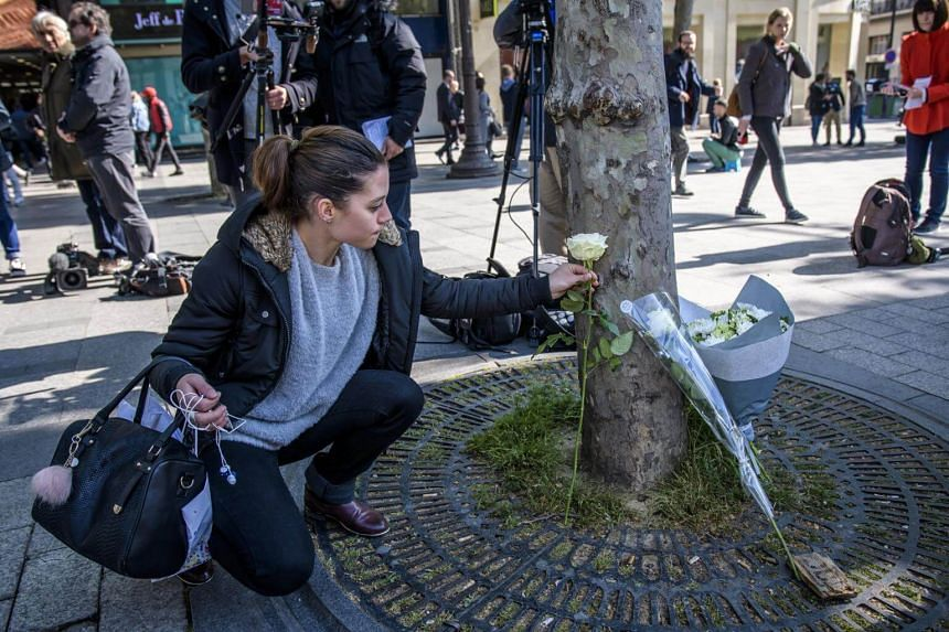 A woman places a flower to pay tribute to the killed French policeman at the Champs Elysee avenue in Paris, France, on April 21, 2017.