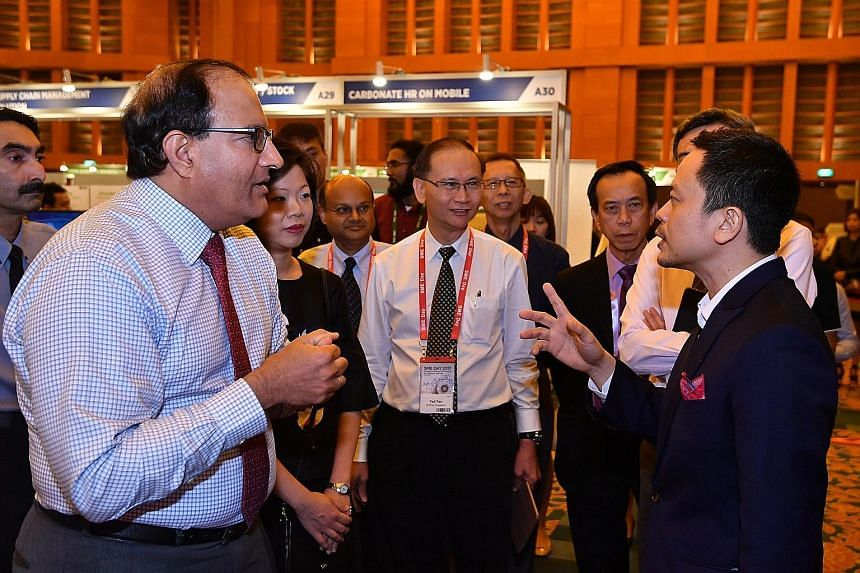 Mr S. Iswaran, Minister for Trade and Industry (Industry), with Mr Eric Lew, executive director of Wong Fong Industries Group, at the exhibition yesterday. The minister urges SMEs to embrace technology solutions.
