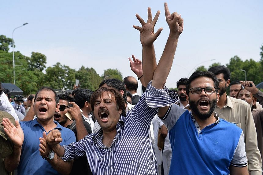 Supporters of opposition leader Imran Khan calling for the resignation of Pakistani Prime Minister Nawaz Sharif (above) after the court verdict in Islamabad yesterday. The investigation into Mr Sharif concerns the offshore wealth of his family.