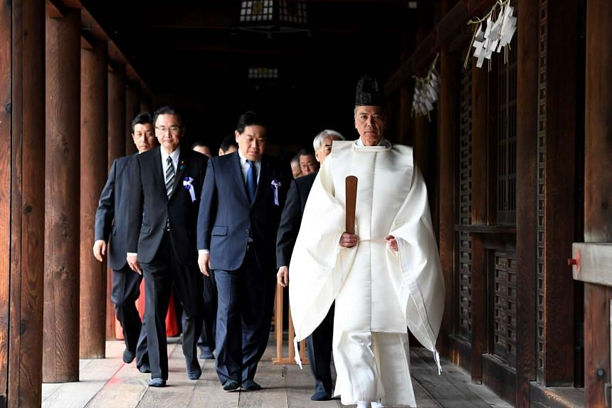 A shinto priest leads Japanese lawmakers after their prayer at the altar of Yasukuni Shrine during the shrine's spring festival in Tokyo on April 21, 2017.