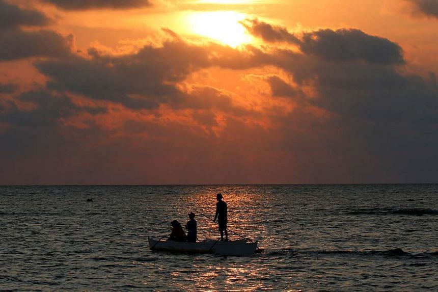 Philippine fishermen steering a dinghy during sunset as they fish inside the shoal of the disputed Scarborough Shoal on April 5, 2017.