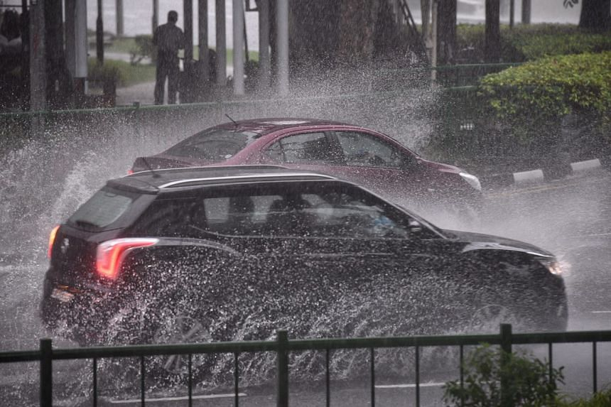 Cars were splashing through puddles of water covering Upper Cross Street outside the State Courts.