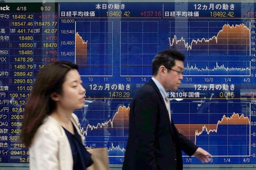 Pedestrians walking in front of a display flashing charts of the Nikkei key index of the Tokyo Stock Exchange in Tokyo.