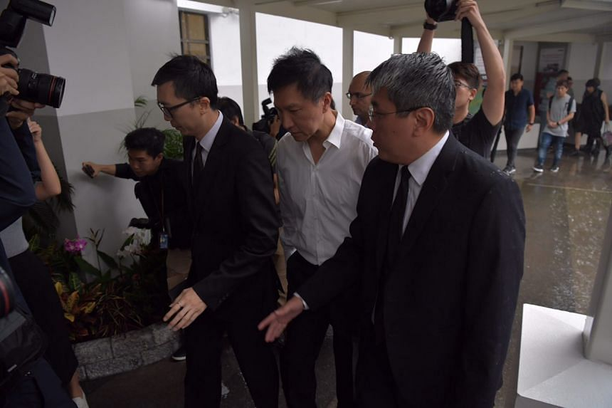City Harvest Church founder Kong Hee was flanked by two men as he entered the State Courts building at around 8.30am even as it rained outside.
