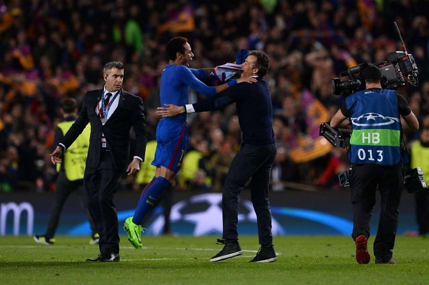 Barcelona's coach Luis Enrique (2nd right) celebrates with Barcelona's Brazilian forward Neymar their 6-1 victory between FC Barcelona and Paris Saint-Germain FC at the Camp Nou stadium in Barcelona on March 8, 2017.