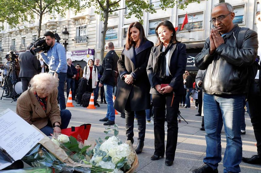 Mayor of Paris Anne Hidalgo (centre left) standing as she pays her respect at the site of a shooting on the Champs Elysees in Paris, on April 21, 2017.