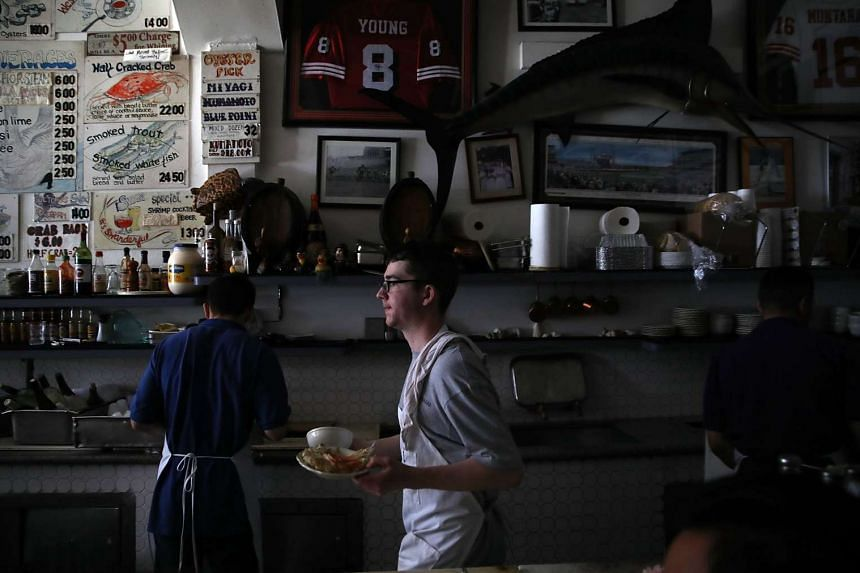 A waiter at Swan Oyster Depot carries food to customers during a citywide power outage on April 21, 2017 in San Francisco.