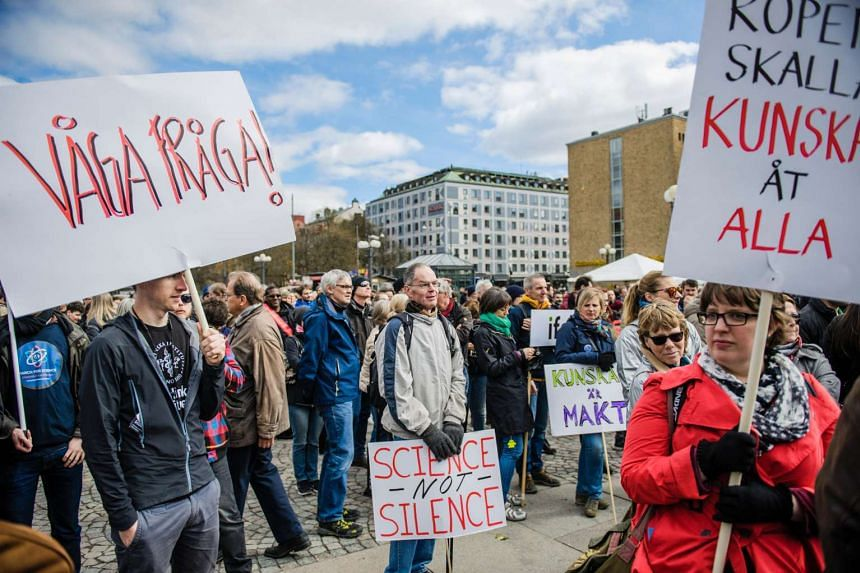 Demonstrators hold placards during the worldwide event March for Science in Stockholm, on April 22, 2017.
