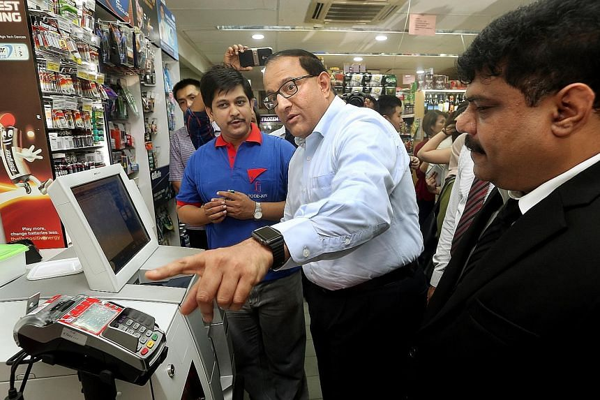 General manager S. Janakiraman (in blue) of Food-Joy, among the first micro-retailers here to adopt self-checkout machines, with Minister S. Iswaran (centre) during a learning journey for such retailers yesterday.