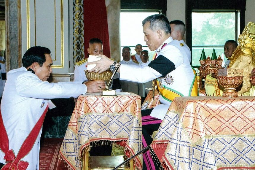 Thai King Maha Vajiralongkorn returning the new Constitution to Prime Minister Prayut Chan-o-Cha after signing it at the Ananta Samakhom Throne Hall in Bangkok.