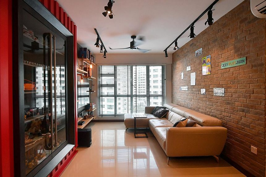The living room of Mr Jefferson Lee and Ms Sheryl Tian has red shipping container-inspired storage (above) which displays their knick-knacks and toys.