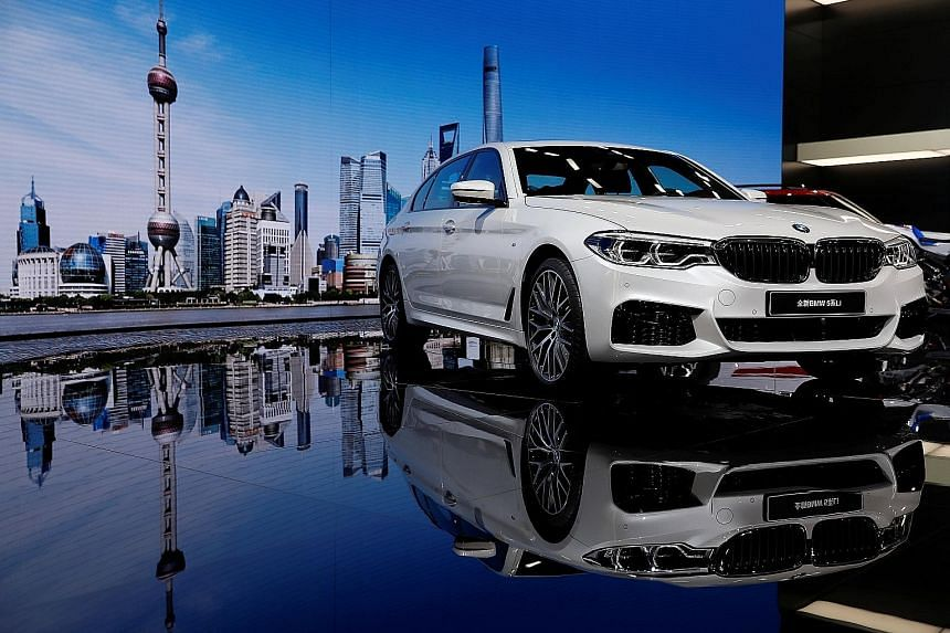 MG Motor's E-motion concept car, BMW's 5-Series Li (above) and the new Ford Mustang on display at the Shanghai Auto Show.