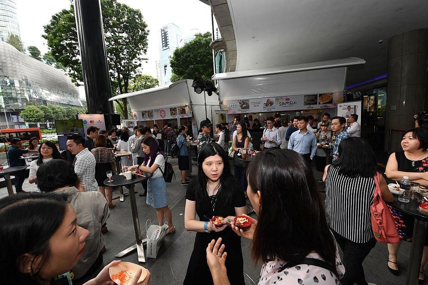 At the Local Gourmet Fiesta outside Shaw House, visitors can tuck into salted egg chicken burger, tempura kimchi popiah and other delicious food.