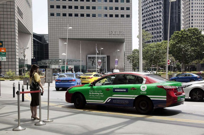 A customer hails a taxi featuring an advertisement for Grab, at the Suntec City taxi stand in Singapore, on Oct 31, 2016.