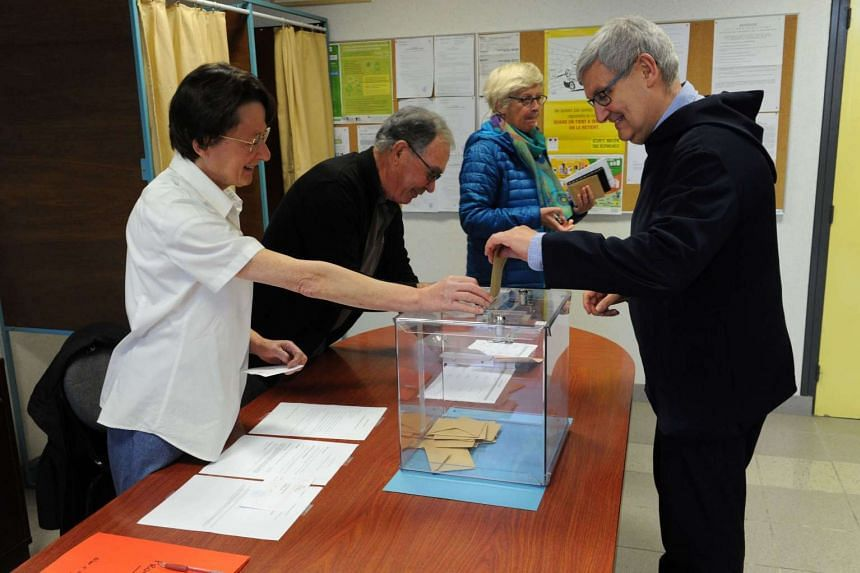 A monk from Saint-Guenole Abbey casting his ballot at a polling station in Landevenec, western France, on April 23, 2017.