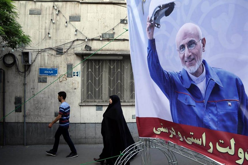 Iranians walk behind a huge election campaign poster of Iranian presidential conservative candidate Mostafa Mir-Salim in front of his office in Tehran, Iran, on April 23, 2017.