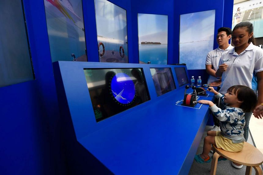 Isaiah Kum, 2.5 years old, trying out the ship bridge simulator at the Singapore Maritime Week exhibition at Marina Square.