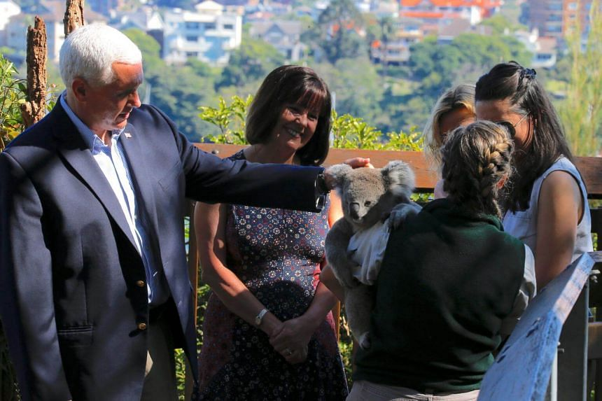US Vice President Mike Pence pats a koala being held by a keeper as his wife Karen and daughters Charlotte and Audrey look on during a visit to Taronga Zoo in Sydney, Australia, on April 23, 2017.