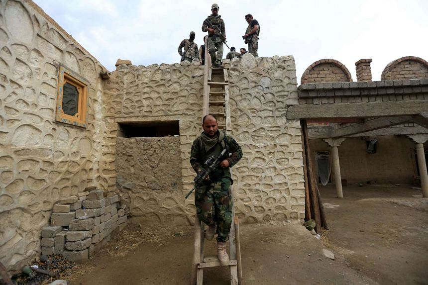 Afghan Special Forces walk down from the roof of a house which was used by suspected Islamic State militants at the site where the bomb was dropped.