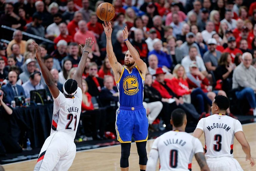 Stephen Curry (second from left) shoots the ball over Noah Vonleh (left) during Game Three of the Western Conference Quarterfinals of the 2017 NBA Playoffs at Moda Center in Portland, Oregon, on April 22, 2017.