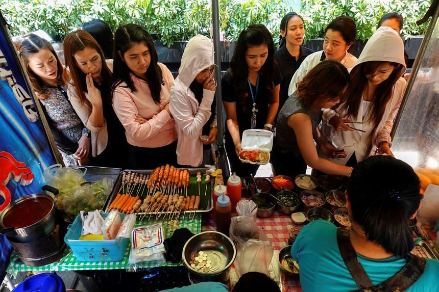 People queue to buy their lunch at a street food stall in Bangkok.