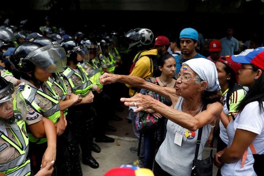 A woman confronts riot police during a rally to honour victims of violence during a protest against Venezuela government, April 22, 2017.