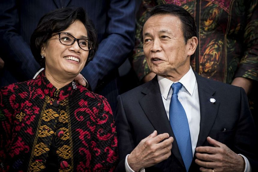 Taro Aso (right) and Indonesian finance minister Sri Mulyani Indrawati speak before a group photograph at the spring meetings of the MF and World Bank in Washington on April 22, 2017.