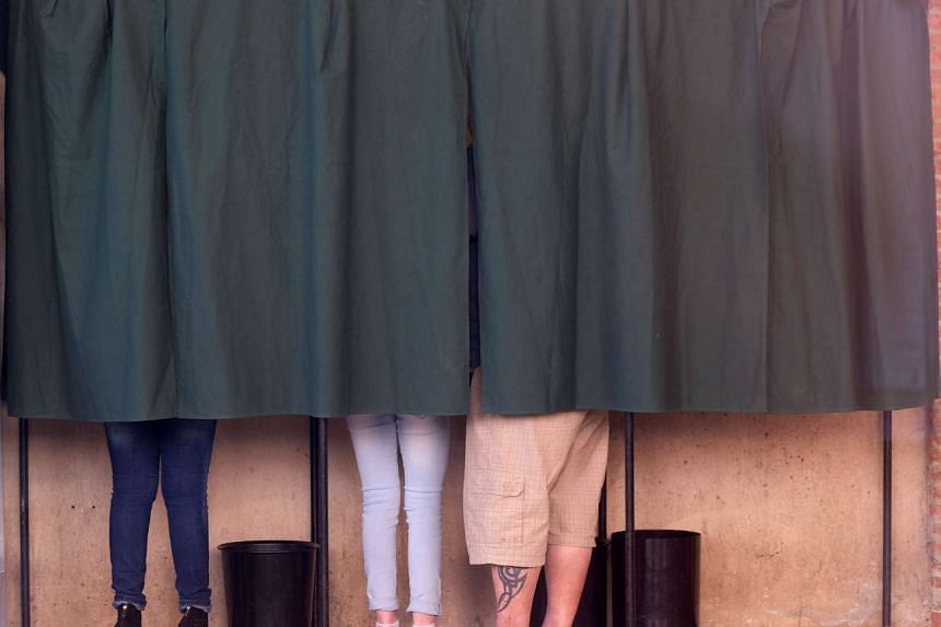 People stand in a voting booth in Villefranche-de-Lauragais, near Toulouse, on April 23, 2017 during the first round of the French Presidential election.