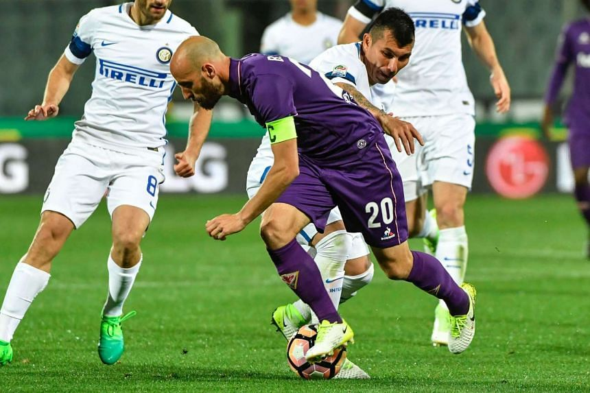Fiorentina midfielder Borja Valero (centre) fights for the ball with Inter Milan midfielder Gary Medel during the match on April 22.