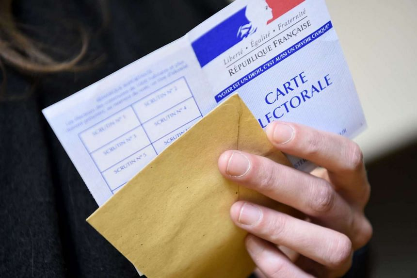 A woman holds her electoral ID card as she arrives to vote at a polling station in Paris on April 23, 2017.