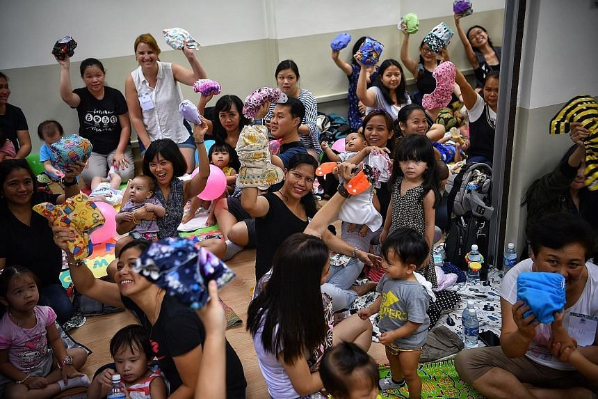 Participants holding up cloth diapers before The Great Cloth Diaper Change in Bukit Batok yesterday. Parents said cloth diapers are environmentally friendly and cost effective. The event coincided with Earth Day, which is observed on April 22 to cele