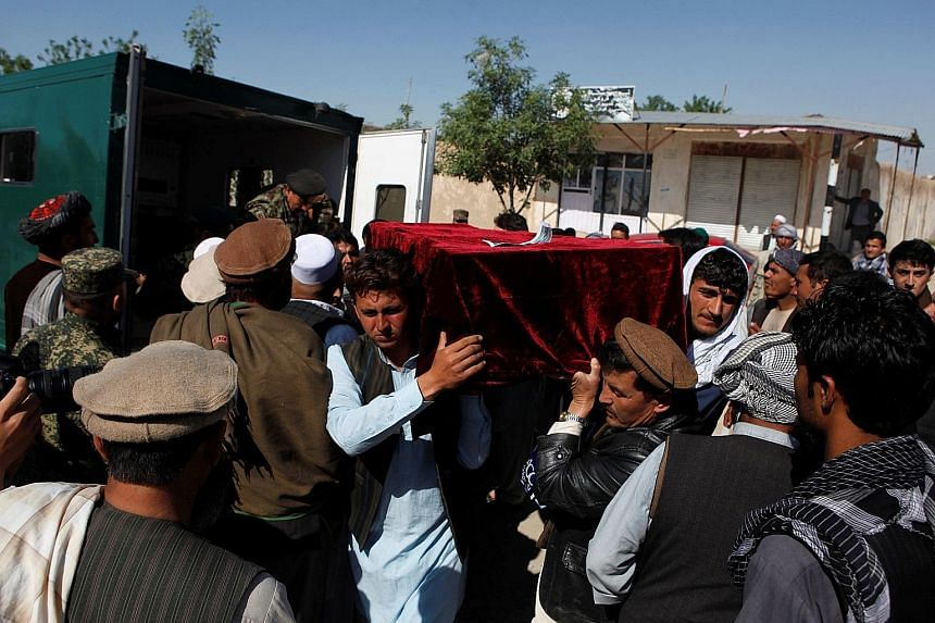 Relatives carrying a victim's coffin yesterday, a day after a Taleban attack on an army base in Mazar-i-Sharif in northern Afghanistan. The attack began at around 1pm in a crowded area where soldiers were leaving Friday prayers or eating lunch.