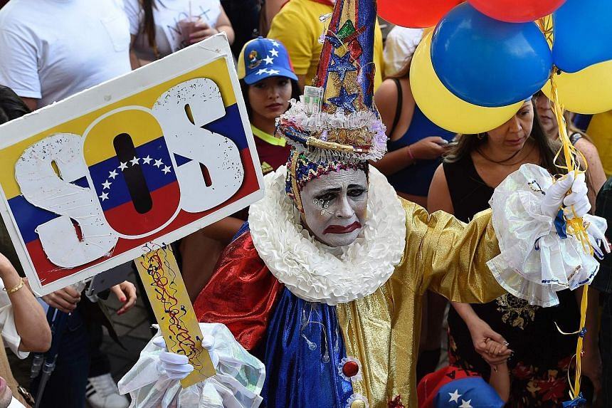 Protesters in the US state of Florida at a rally against the Venezuelan government last week. Venezuela is in the grip of escalating violence as President Nicolas Maduro faces calls for his ouster from the opposition. He says the protests against him