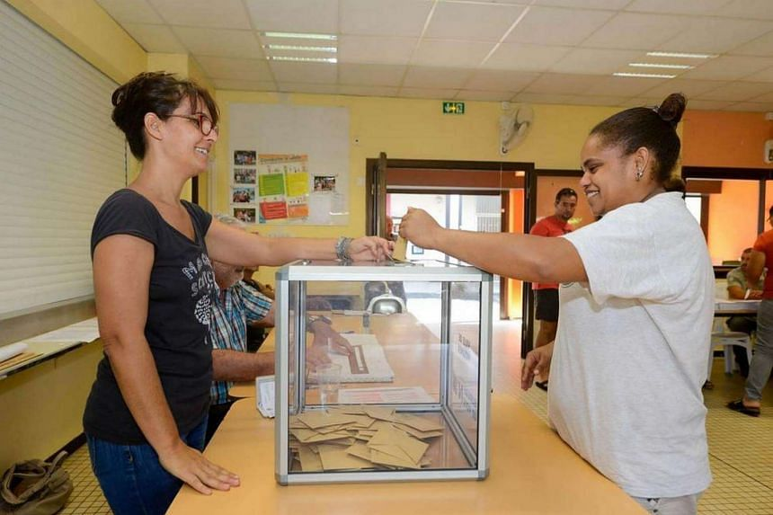 Voters casting their ballots at a polling station for the French presidential election, on April 23, 2017, in Noumea, capital of the French overseas territory of New Caledonia.