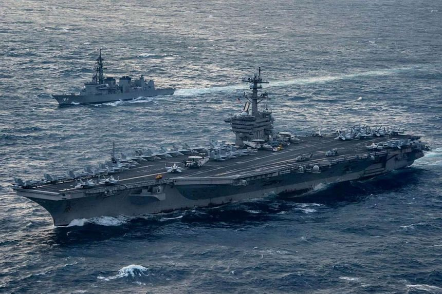Aircraft carrier USS Carl Vinson (foreground),as it transits the East China Sea with the Japan Maritime Self-Defense Force Murasame-class destroyer JS Samidare, on March 9, 2017.