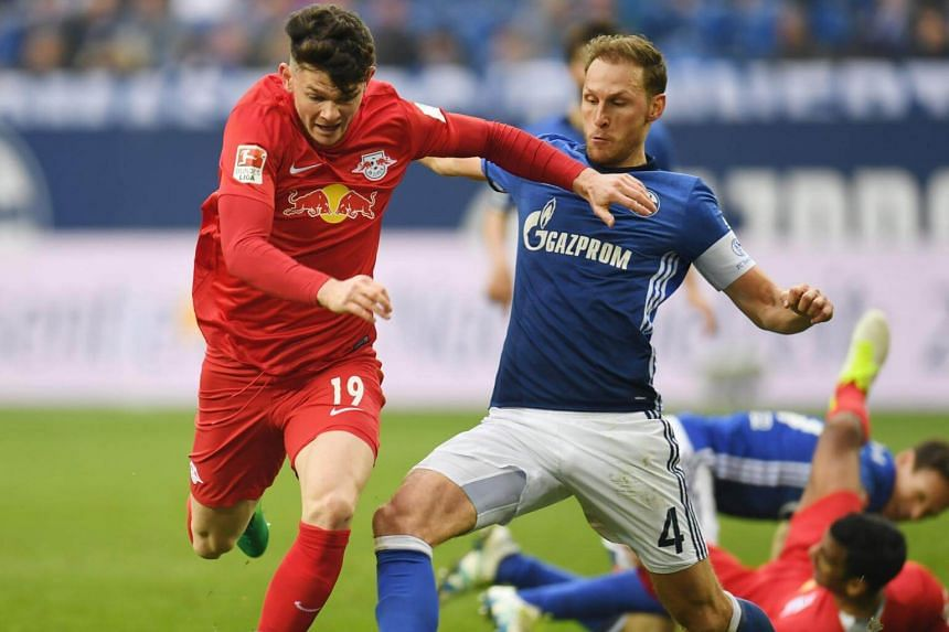 Schalke's defender Benedikt Hoewedes (right) and Leipzig's midfielder Oliver Burke vie for the ball in the match on April 23, 2017.